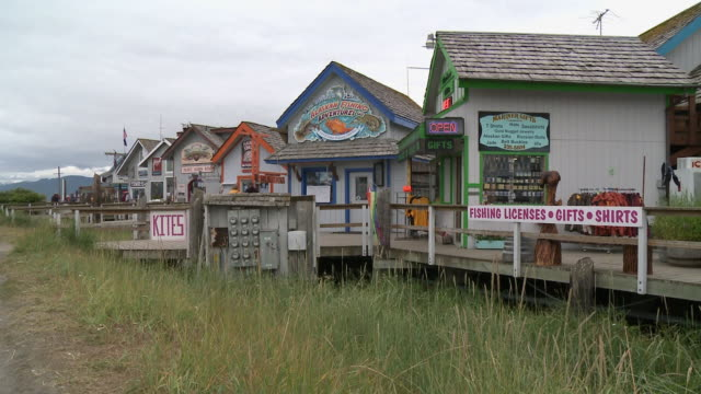 """wooden buildings with colourful facades and signage housing various shops and businesses on homer spit, homer, kenai peninsula, alaska."" - homer alaska stock videos & royalty-free footage"