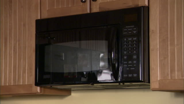 wooden cabinets surround a kitchen's microwave oven. - microwave stock videos & royalty-free footage