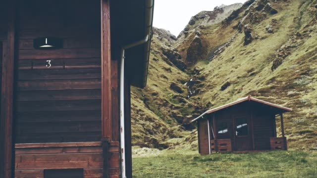 wooden cabins surrounded by mountains - capanna di legno video stock e b–roll