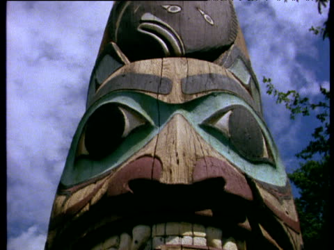 wooden carved face tilt up along colourful native totem pole with clouds and blue sky above - indigenous peoples of the americas stock videos & royalty-free footage
