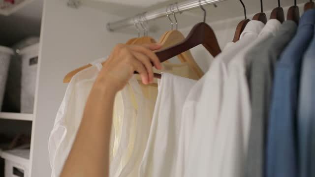 vidéos et rushes de handers en bois de vêtements, fermez-vous vers le haut de la main de la femme choisissant des vêtements dans le rail suspendu dans la salle de bains, garde-robe est remplie avec des vêtements dans la salle - rangement