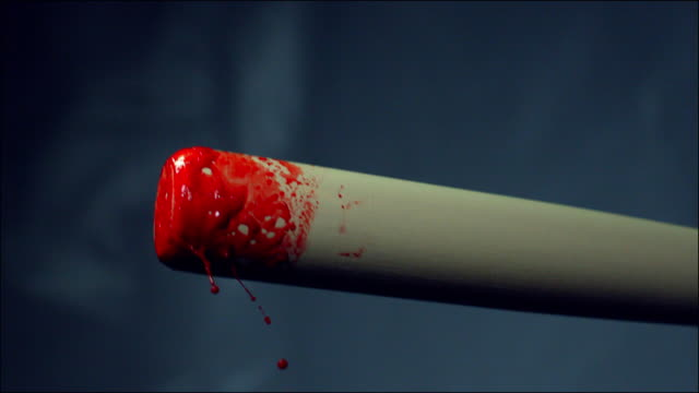 A wooden club covered in blood swings upwards in slow motion