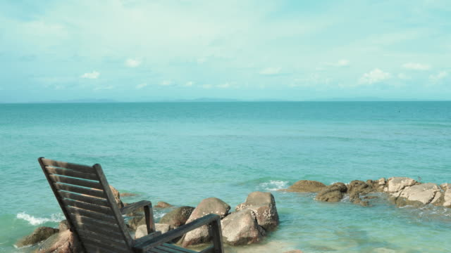 vídeos y material grabado en eventos de stock de madera silla cómoda en la playa claro cielo y mar - tumbona