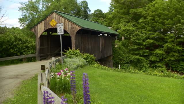 ws pan wooden covered bridge in rural landscape / morristown, vermont, usa - überdachte brücke brücke stock-videos und b-roll-filmmaterial