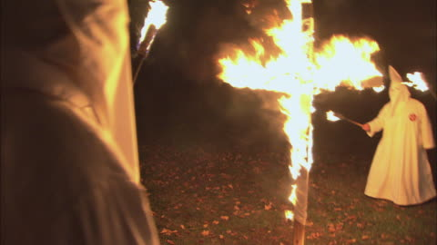 vidéos et rushes de recreation wooden cross is engulfed in flames as kkk members in white robes are standing in a semi-circle around it / rockford, illinois, united states - injustice
