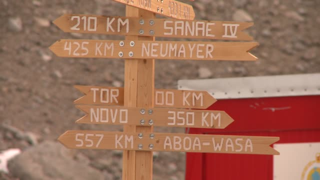 a wooden directional sign near the troll research station displays the distance to different towns in antarctica. available in hd. - directional sign stock videos & royalty-free footage