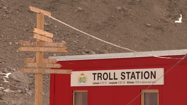 A wooden directional sign near the Troll research station displays the distance to different towns in Antarctica. Available in HD.