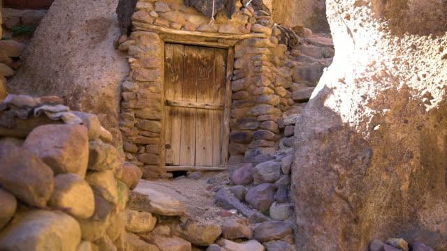 vidéos et rushes de wooden door and walkways built within rock - ouverture du diaphragme