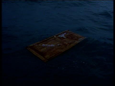 Wooden door floating in sea