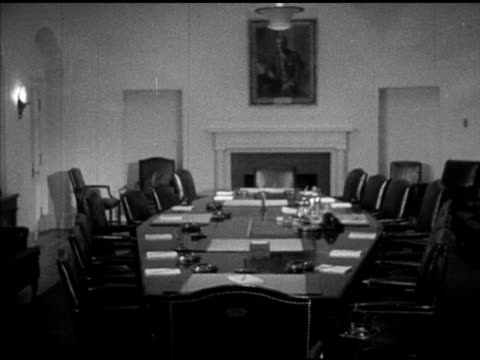 Wooden door opening REVEALS conference table w/ fireplace portrait painting of former President Woodrow Wilson hanging above mantle PAN Table set w/...