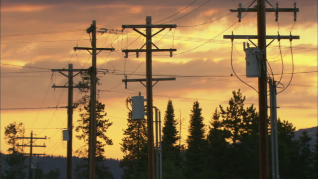 ms wooden electrical power poles and wire against sunset sky / wyoming, usa - electricity pylon stock videos & royalty-free footage