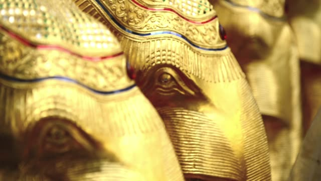 wooden elephant decorated in gold paint and glass mosaic at erawan shrine - エラワン聖堂点の映像素材/bロール
