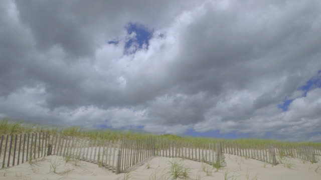 vidéos et rushes de ws wooden fence on wiborg beach, cloudy sky seen in background / east hampton, suffolk county, new york state, united states - long island