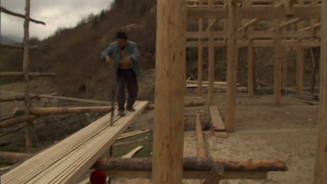 ms td tu wooden frame of building under construction and two men cutting plank with hand saw, baiman village, sichuan, china - hand saw stock videos and b-roll footage