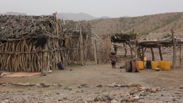 Wooden huts and child carrying load