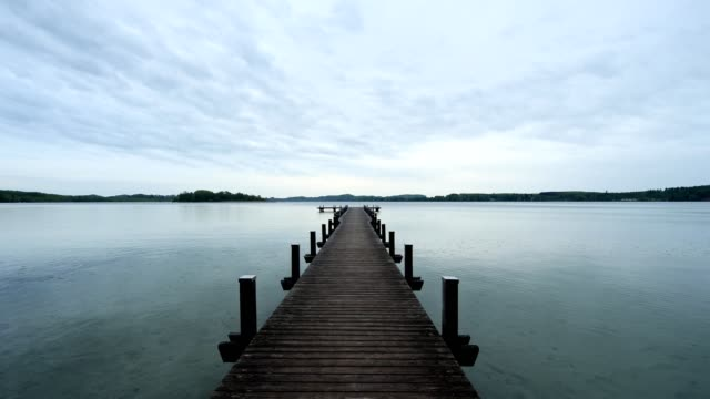 vídeos de stock e filmes b-roll de wooden jetty at cloudy morning on lake worthsee, fuenfseenland, upper bavaria, germany - pontão