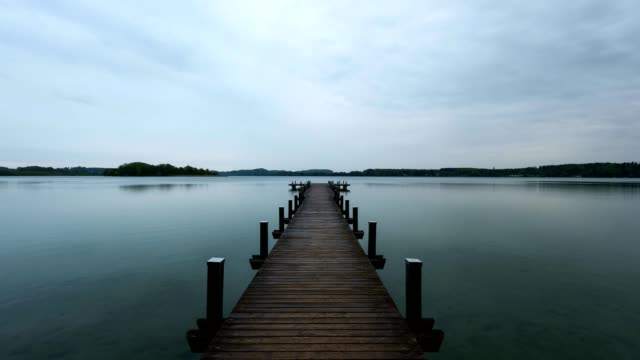 wooden jetty at rain on lake worthsee, fuenfseenland, upper bavaria, germany - jetty stock videos & royalty-free footage
