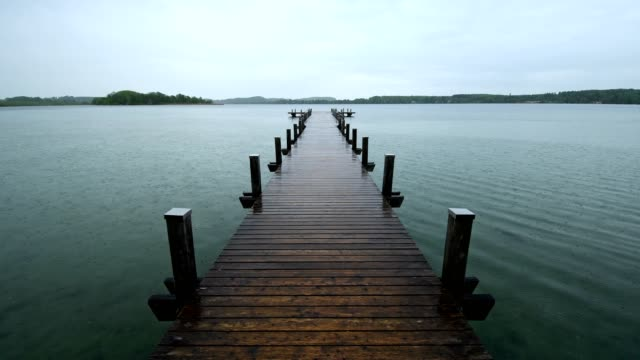 Wooden jetty at rainy morning on Lake Worthsee, Fuenfseenland, Upper Bavaria, Germany