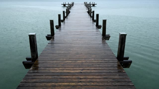 vídeos de stock e filmes b-roll de wooden jetty at rainy morning on lake worthsee, fuenfseenland, upper bavaria, germany - pontão