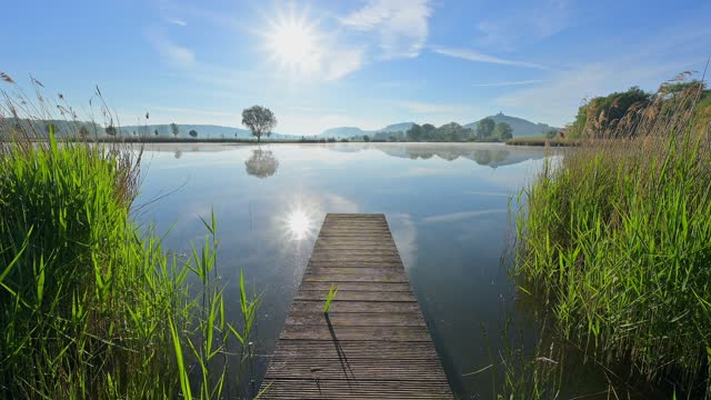 wooden jetty at sunrise with wachsenburg castle, drei gleichen, ilm district, thuringia, germany - jetty stock videos & royalty-free footage