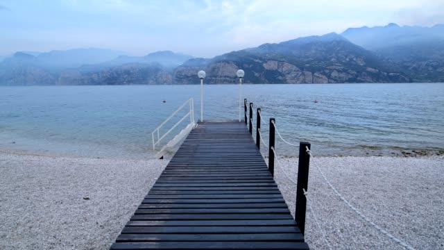 wooden jetty on lake in the morning, malcesine, lake garda, lago di garda, veneto, italy - lago stock videos & royalty-free footage
