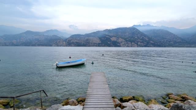 wooden jetty on lake in the morning, malcesine, lake garda, lago di garda, veneto, italy - 不在点の映像素材/bロール