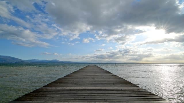 wooden jetty on the lake in the morning, sirmione, brescia, lake garda, lago di garda, lombardy, lombardei, italy - lago stock videos & royalty-free footage