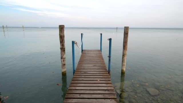 wooden jetty on the lake, sirmione, brescia, lake garda, lago di garda, lombardy, lombardei, italy - 不在点の映像素材/bロール