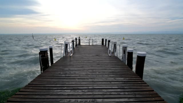 stockvideo's en b-roll-footage met wooden jetty on the lake with strong waves, sirmione, brescia, lake garda, lago di garda, lombardy, lombardei, italy - steiger pier