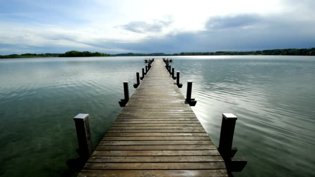 wooden jetty, sun breaking after rain through the clouds, on lake worthsee, fuenfseenland, upper bavaria, germany - jetty stock videos & royalty-free footage