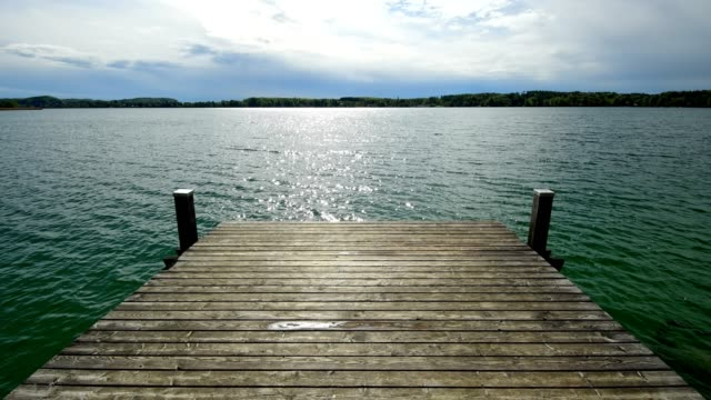 wooden jetty, sun breaking after rain through the clouds, on lake worthsee, fuenfseenland, upper bavaria, germany - pier stock videos & royalty-free footage