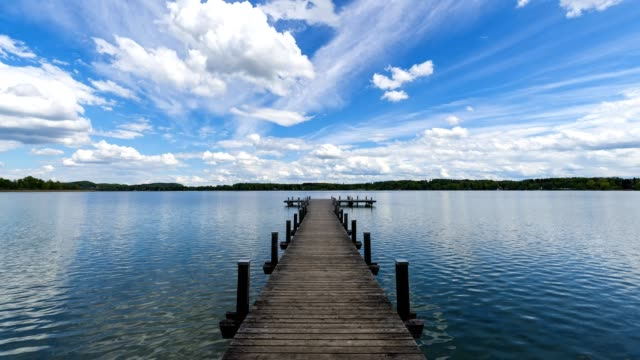 wooden jetty with clouds on lake worthsee, fuenfseenland, upper bavaria, germany - jetty stock videos & royalty-free footage