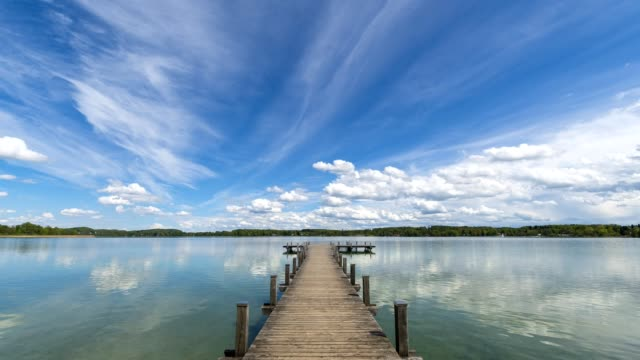 vídeos de stock e filmes b-roll de wooden jetty with clouds on lake worthsee, fuenfseenland, upper bavaria, germany - docas
