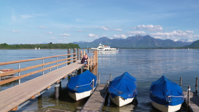 Wooden Jetty with tourboat in background on lake Chiemsee with view to Bavarian Alps. Chiemsee, Bavaria, Germany.