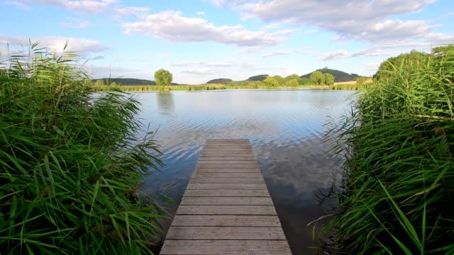 wooden jetty with wachsenburg castle and lake, drei gleichen, ilm district, thuringia, germany - turingia video stock e b–roll