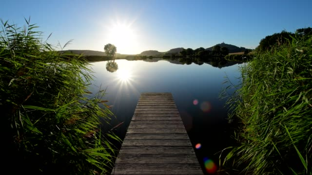 wooden jetty with wachsenburg castle reflecting in lake with morning sun, drei gleichen, ilm district, thuringia, germany - turingia video stock e b–roll