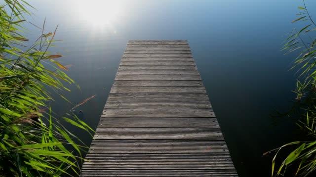 vidéos et rushes de wooden jetty with wachsenburg castle reflecting in lake with morning sun, drei gleichen, ilm district, thuringia, germany - en bois