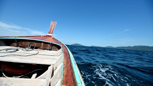 Wooden long-tail boat sailing on blue sea to the island