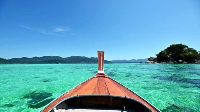 wooden long-tail boat sailing on emerald sea to the island - facade stock videos & royalty-free footage
