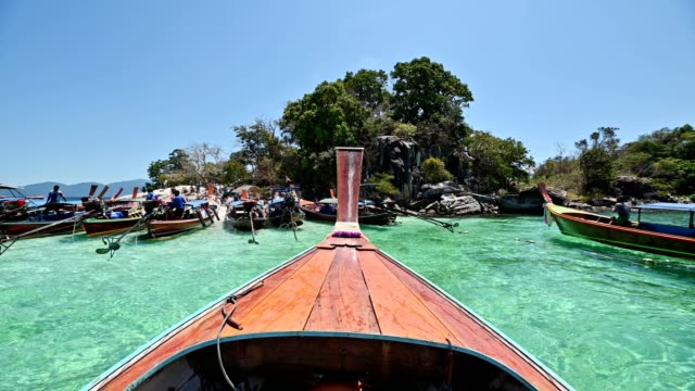 Wooden long-tail boat sailing on emerald tropical sea at lipe island