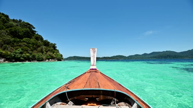 wooden long-tail boat sailing on emerald tropical sea at lipe island - phuket stock videos & royalty-free footage