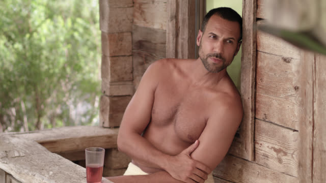 wooden outdoor sauna hut - sporty tanned buff man with dark short hair in his 30s sitting in front of the shack, relaxing after purging in the heat and drinking refreshing healthy beverage out of a cup, enjoying the moment of digital detox in the nature - タオルにくるまる点の映像素材/bロール