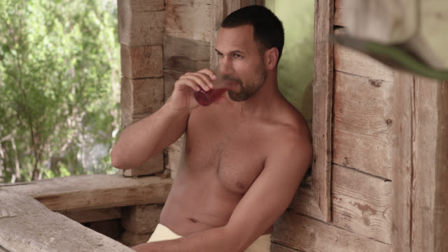 stockvideo's en b-roll-footage met wooden outdoor sauna hut - sporty tanned buff man with dark short hair in his 30s sitting in front of a shack, relaxing after purging in the heat and drinking refreshing healthy beverage out of a cup, enjoying the moment of digital detox in the nature - in een handdoek gewikkeld
