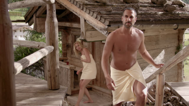 wooden outdoor sauna hut with rocks on roof on a sunny day – door opens and a sporty man in his 30s and a blonde woman with long hair wearing towels only exiting the sauna, closing the door and walking up the stairs out of the frame – camera tilts down - sauna stock videos & royalty-free footage
