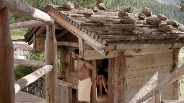 wooden outdoor sauna hut with rocks on the roof – door opens and a sporty man in his 30s with short dark hair wearing a towel only exiting the sauna, blonde girl indoors, closing the door and walking up the stairs out of the frame – camera tilts down