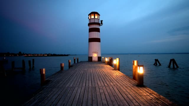 wooden pier with lighthouse at dusk, podersdorf, neusiedlersee, burgenland, austria - footbridge stock videos & royalty-free footage