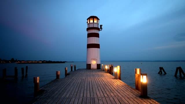 wooden pier with lighthouse at dusk, podersdorf, neusiedlersee, burgenland, austria - österrikisk kultur bildbanksvideor och videomaterial från bakom kulisserna