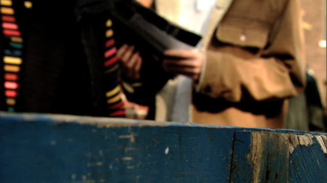 wooden police saw horse barrier, soft focus bodies of people in vest & sweater, open jacket, citizens standing in line behind barricade waiting to... - 2008 stock-videos und b-roll-filmmaterial
