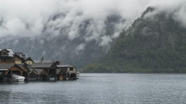 wooden residental building in famous hallstatt mountain village at raining day in summer - village stock videos & royalty-free footage