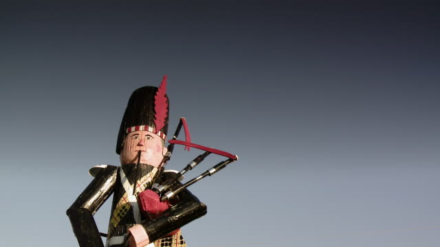 A wooden sculpture of a bagpipe player